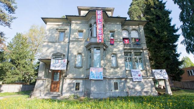 Ein altes Haus von aussen mit Transpartenen geschmückt.