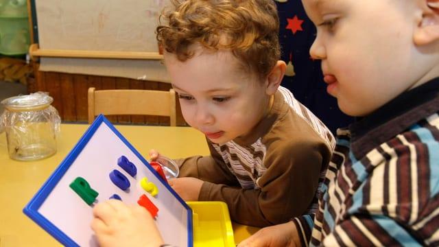 Zwei Dreijährige spielen mit bunten Buchstaben aus Plastik.