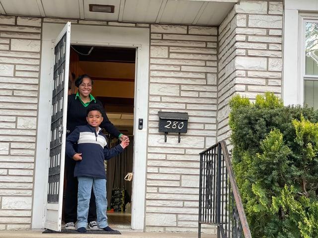 Mutter und Sohn stehen im Eingang ihres Hauses.