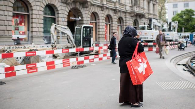 Frau mit Kopftuch und Tasche mit Schweizer Kreuz