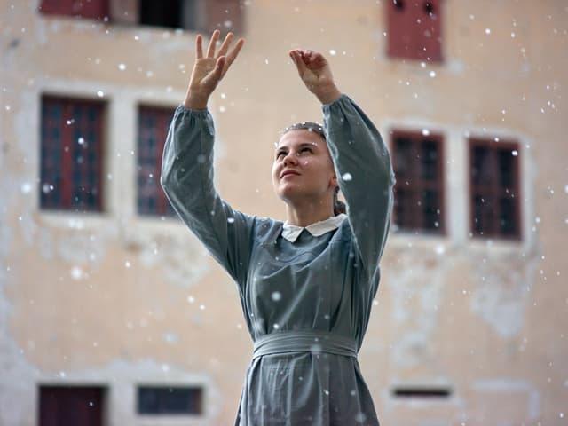 Ein Mädchen steht draussen und greift nach herabfallenden Schneeflocken.