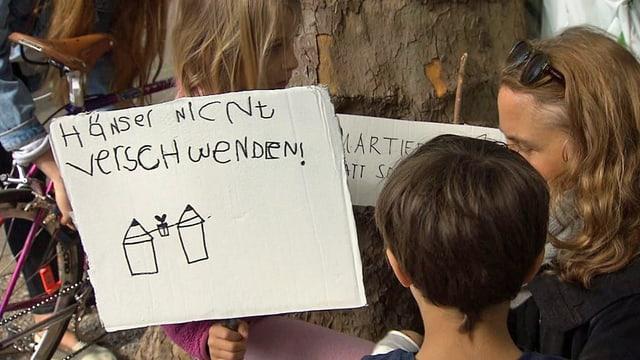 Protestierende mit einem Plakat: Häuser nicht verschwenden.