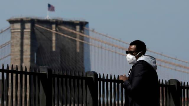 Mann mit Maske schaut zur Brooklyn Bridge.