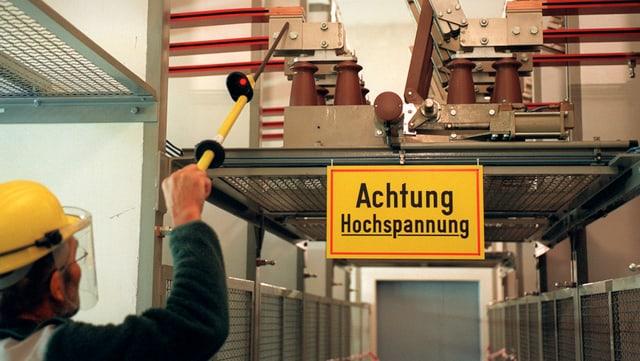 Ein Arbeiter misst mit einem Stab wohl die Spannung in einer Trafostation eines Elektrizitätswerkes.