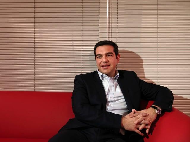 Alexis Tsipras auf einem roten Sofa sitzend.