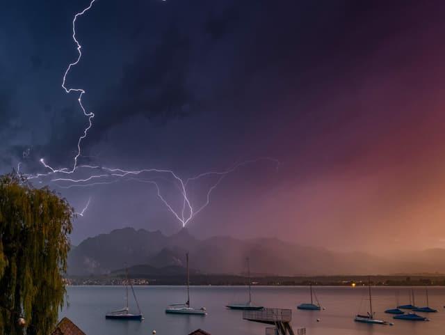 Blick vom Ufer aus über einen See auf Bergkette, wo Blitze mehrmals am selben Gipfel einschlagen.