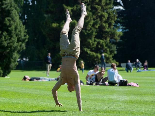 Ein Mann mit nacktem Oberkörper macht im Frühling auf einer Wiese am Zürichsee einen Handstand.