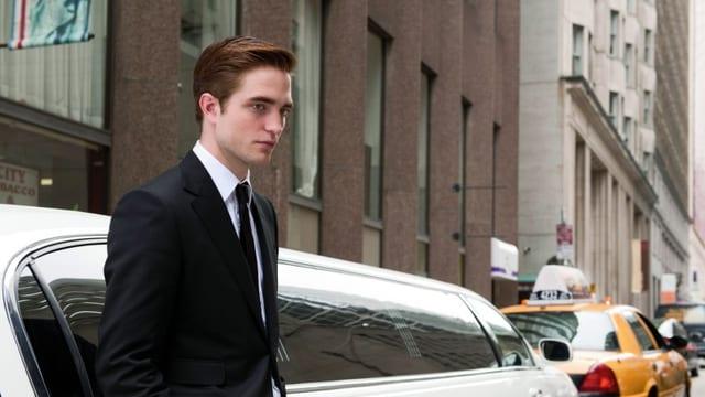 Ein junger Mann steht mit einem schicken Anzug bekleidet vor einer Limousine.