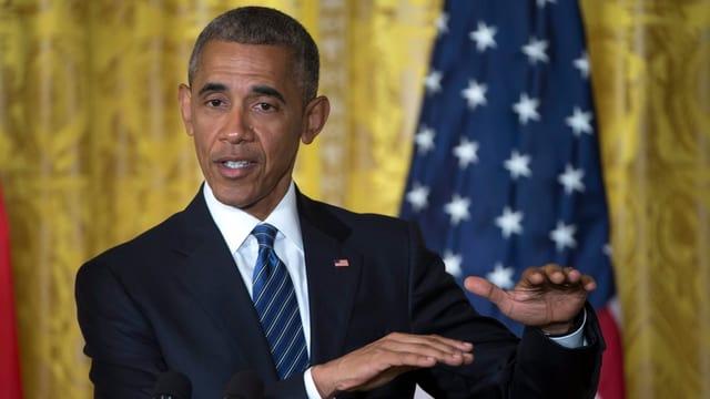 Obama vor einem goldenen Vorhang und US-Flagge mit bestimmtem Blick und gestikulierenden Händen.