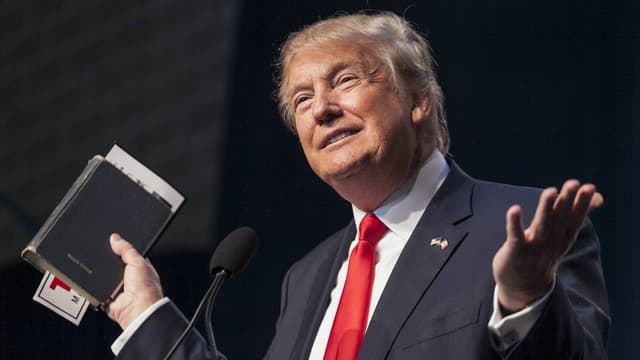 Trump hält während einer Rede eine Bibel in die Luft.