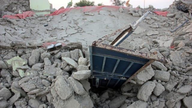 Trümmerfeld aus welchem eine verbogenes Metallstück ragt.