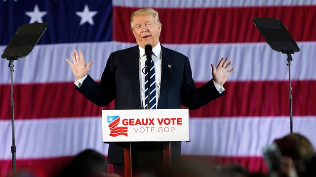 Trump spicht  vor einer riesigen US-Flagge auf einer Bühne in ein Mikrofon, die Arme hat er seitlich erhoben.