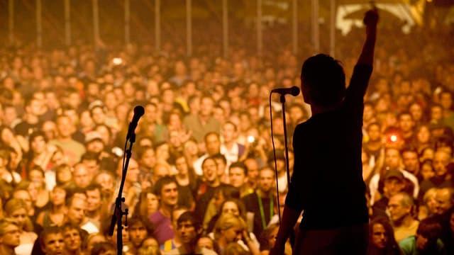 Dunkler Umriss eines Musikers auf der Bühne vor grossem Publikum.