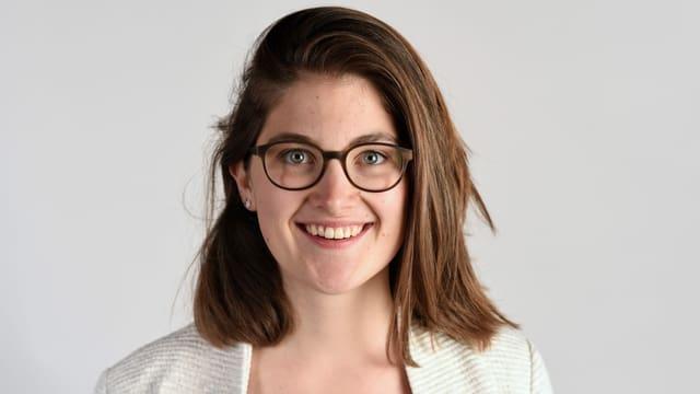 eine junge Frau mit Brille lächelt in die Kamera