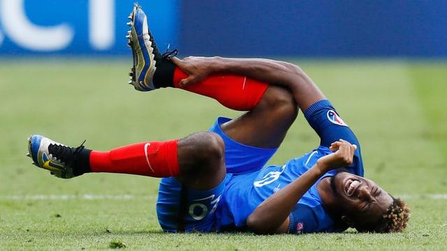 Kingsley Coman wälzt sich auf dem Rasen und hält sich am rechten Knöchel.