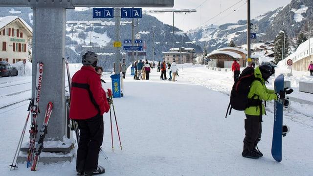 Purtret da persunas cun skis ed aissas ad ina staziun.