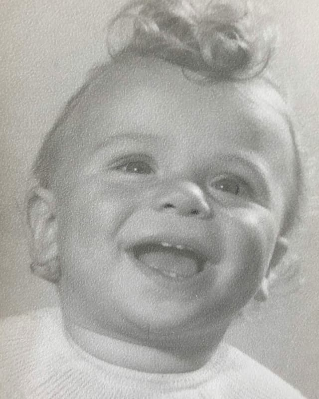 Kleiner Lockenkopf lächelt in die Kamera.