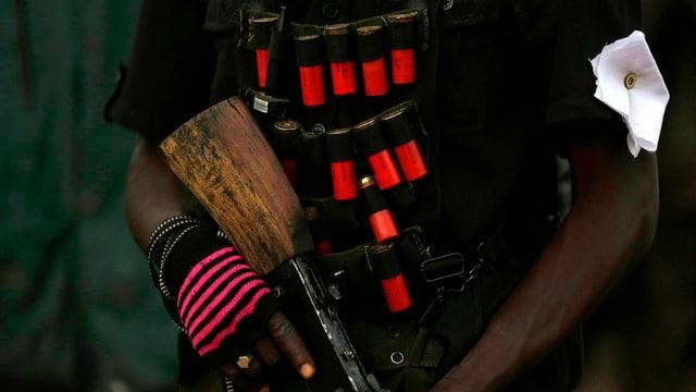 Mann der ein Gewehr in der Hand hält. Schrotpatronenen sind an seiner Weste angehängt.