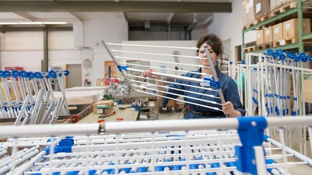 Eine Frau hebt einen Wäscheständer auf einen Stapel.