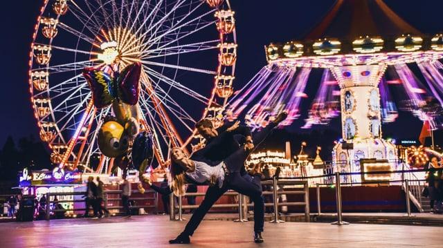 Ein Tänzer und eine Tänzerin nachts vor einem Riesenrad.