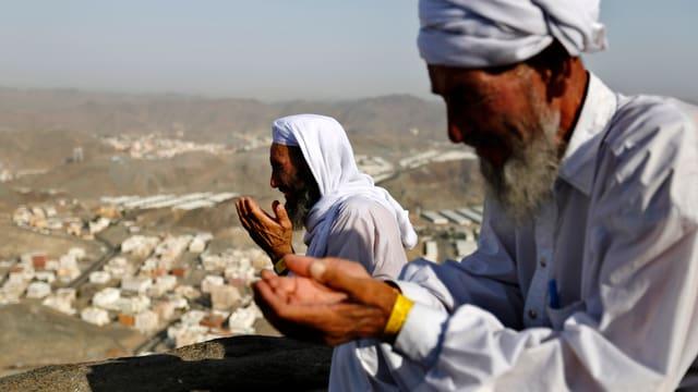 Zwei weiss gekleidete Männer beten auf einem Berg. Im Hintergrund ist die Stadt Mekka zu sehen.