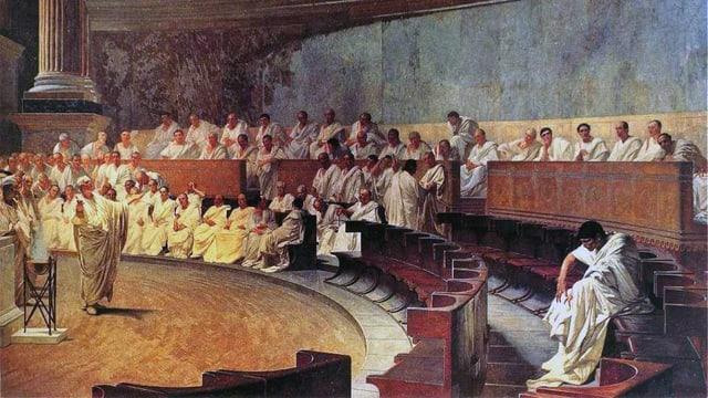 Weiss gekleidete Römer sitzen in einem Saal. In der Mitte spricht eine stehende Person mit ausgebreiteten Armen.