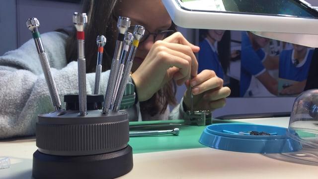 Kind macht eine Übung als Uhrmacherin