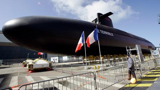 Ein schwarzes U-Boot mit dem Namenszug «Le Terrible» und zwei französischen Flaggen stehen hinter Abschrankungen.