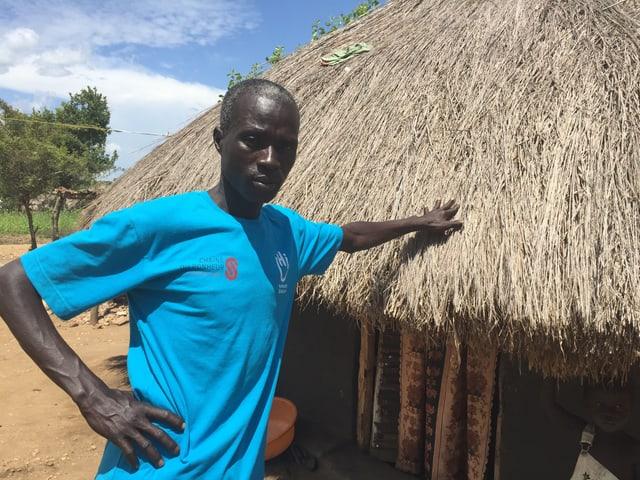 Ein Mann hält stolz seinen Arm auf das Strohdach seiner selbstgebauten Lehmhütte.