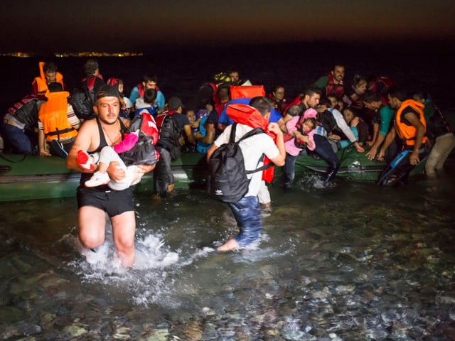 Ein Schlauchboot mit Flüchtlingen kommt an der südöstlichen Küste von Kos an. Ein Mann trägt ein kleines Kind im Arm.