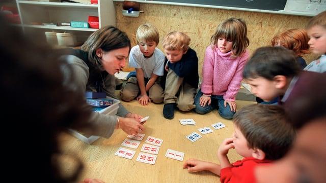 Kinder kauern im Kreis am Boden und schauen Zahlenkarten an.