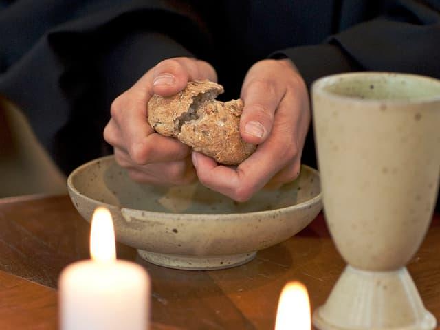 Evangelisch-reformierte Pristerin bricht das Brot fürs Abendmahl.