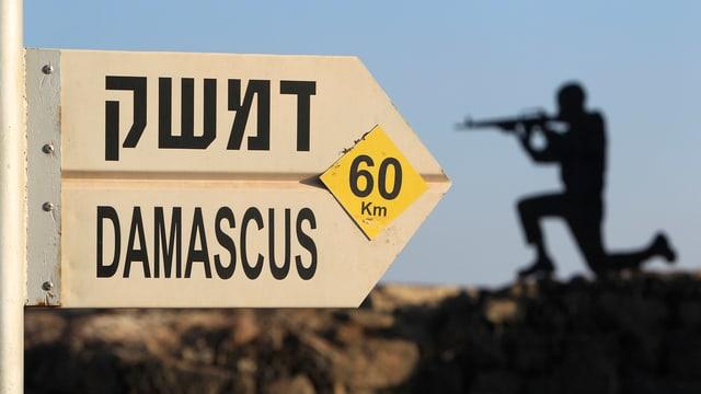 Schild mit der Aufschrift Damascus, 60 km. Daneben die Silhouette einer Silhouettenfigur.
