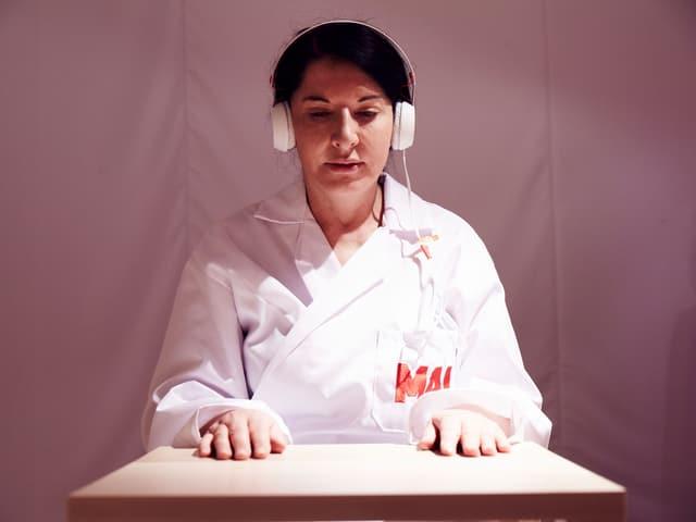 """Marina Abramović sitzt in einem weissen Overall mit der Aufschrift """"MAI"""" an einem Tisch, mit weissem Kopfhörer, die Arme auf den Tisch gelegt,"""