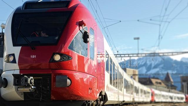 Ein rot-weisser Zug fährt aus einem Bahnhof ab.