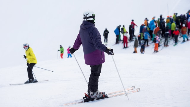 Ein Skifahrer mit Helm beobachtet das Treiben auf der Skipiste.