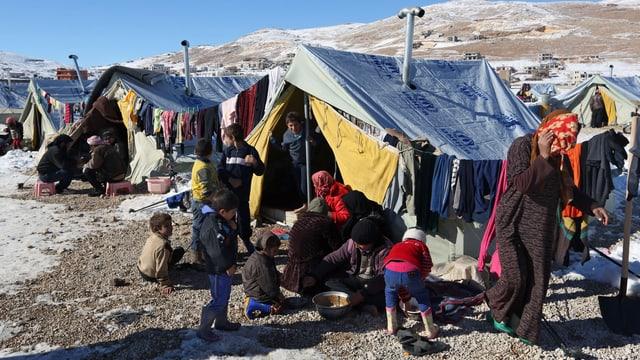 Syrische Flüchtlinge kochen und essen vor ihren Zelten.