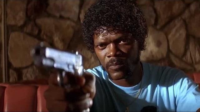 Samuel L. Jackson in einem hellblauen T-Shirt. Er zielt mit einer Pistole auf eine ihm gegenübersitzende Person, die nicht sichtbar ist. Sein BLick ist grimmig.