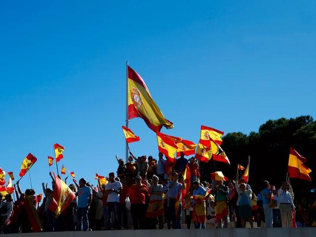 Menschenansammlung und mehrere Spanien-Fahnen vor blauem Himmel.