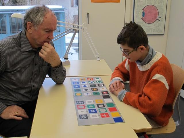 Lehrer Ueli Rüegg und Schüler Vinzenz sitzen sich an einem Tisch gegenüber und betrachten Karten mit unterschiedlichen Formen und Farben darauf.
