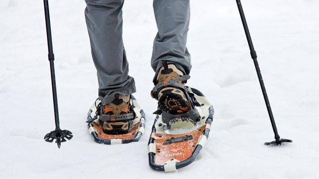 Beine eines Wanderers mit Schneeschuhen