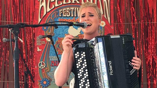 Eine Frau mit Akkordeon singt in eine Mikrophon