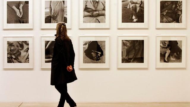 Eine Besucherin vor Fotografien an einer Ausstellung.