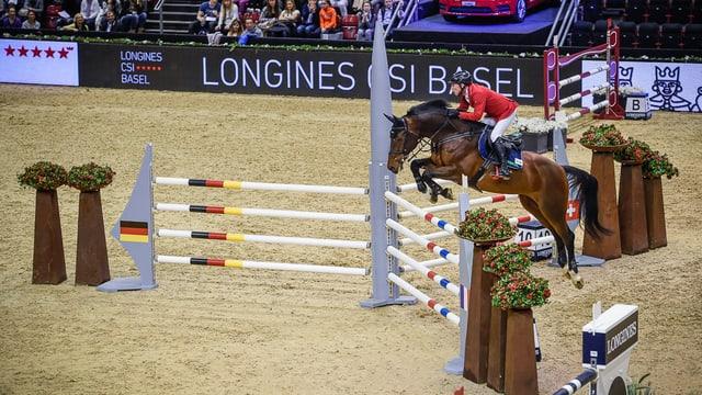 Ein Pferd springt über ein Hindernis. Das Hindernis hat drei Flügel, einer ist in den Farben von Deutschland, einer jenen Frankreichs und der dritte mit den Schweizer Farben. Dazu jeweils die entsprechenden Flaggen.