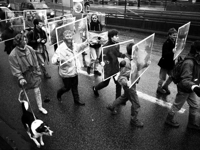 Menschen halten Bilderrahmen vors Gesicht und spazieren auf der Strasse.
