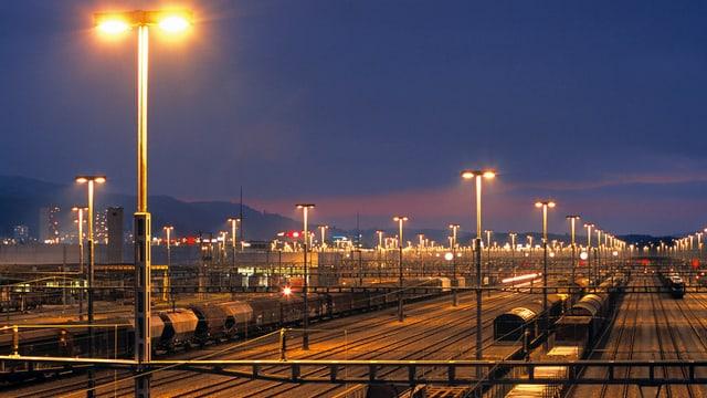 Ein Rangbahnof bei Nacht. Viele Schienen, viele Züge.