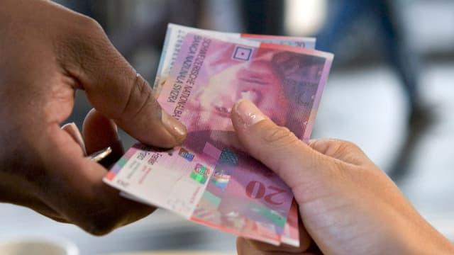 Hände von zwei Personen, welche Geld übergeben.