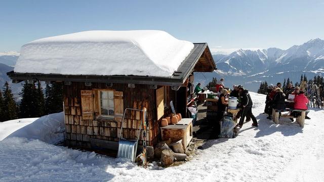Schneesportler sitzen vor Skihütte in der Sonne