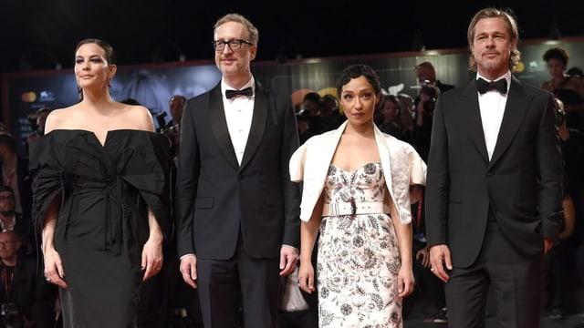 Der elegant angezogene Cast in Kleid und Anzug posiert vor der Kamera.