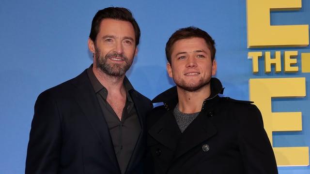 Hugh Jackman und Taran Egerton posieren für ein Foto.